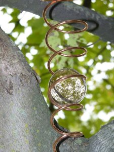A spiral with an orb in a tree shows us the otherworld