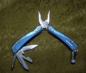 Small multi-tool with flashlight, saw, pliers, knife, etc.