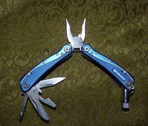 Small multi-tool with flashlight, saw, pliers, knife, etc.