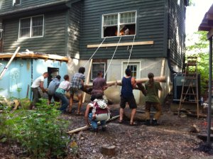 Everyone is lifting the timber frame; we pull with the ropes into the house.