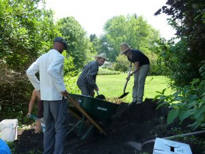 Shoveling compost with friends (note shady location of compost pile - wise placement!)