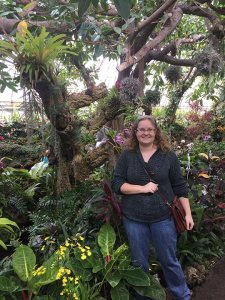 Me on a winter trip to Phipps Conservatory in Pittsburgh, PA. This whimsical space is in the middle of their orchid room!
