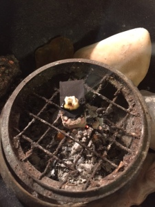 Burning a small amount of red pine resin on a charcoal block in a censer