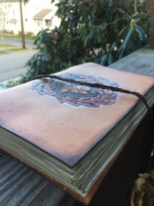 A handcrafted leather book with ecoprinted pages