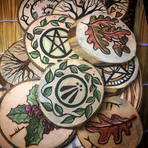 A variety of wood rounds that are burned or painted. These are just about ready to hang!